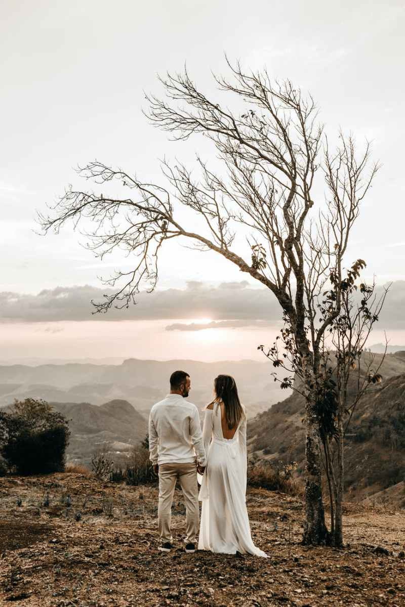 a couple in white dress standing in view of the mountain
