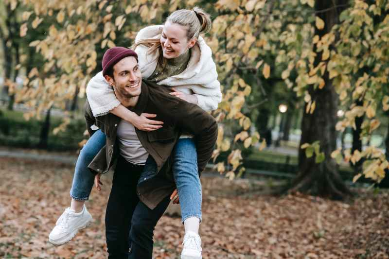 cheerful man giving piggyback ride to smiling girlfriend in park in autumn