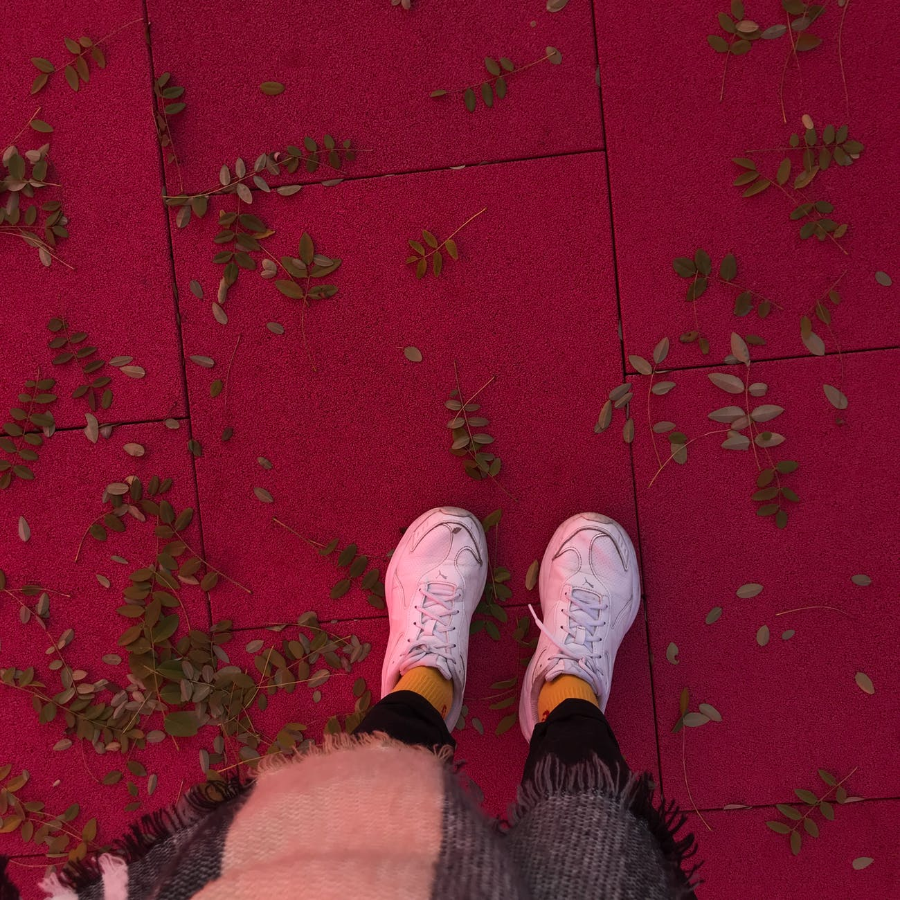 woman standing on red floor with fallen branches