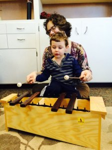 Toddler plays xylophone at Little Notes Baby Music Class Eugene