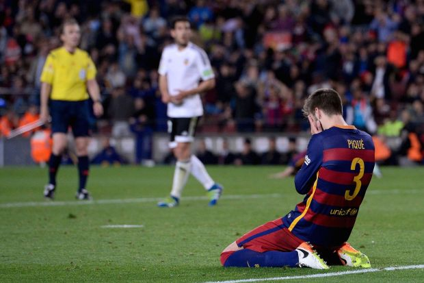 Barcelona's defender Gerard Pique kneels with his face in his hands during the Spanish league football match FC Barcelona vs Valencia CF at the Camp Nou stadium in Barcelona on April 17, 2016. / AFP / JOSEP LAGO (Photo credit should read JOSEP LAGO/AFP/Getty Images)