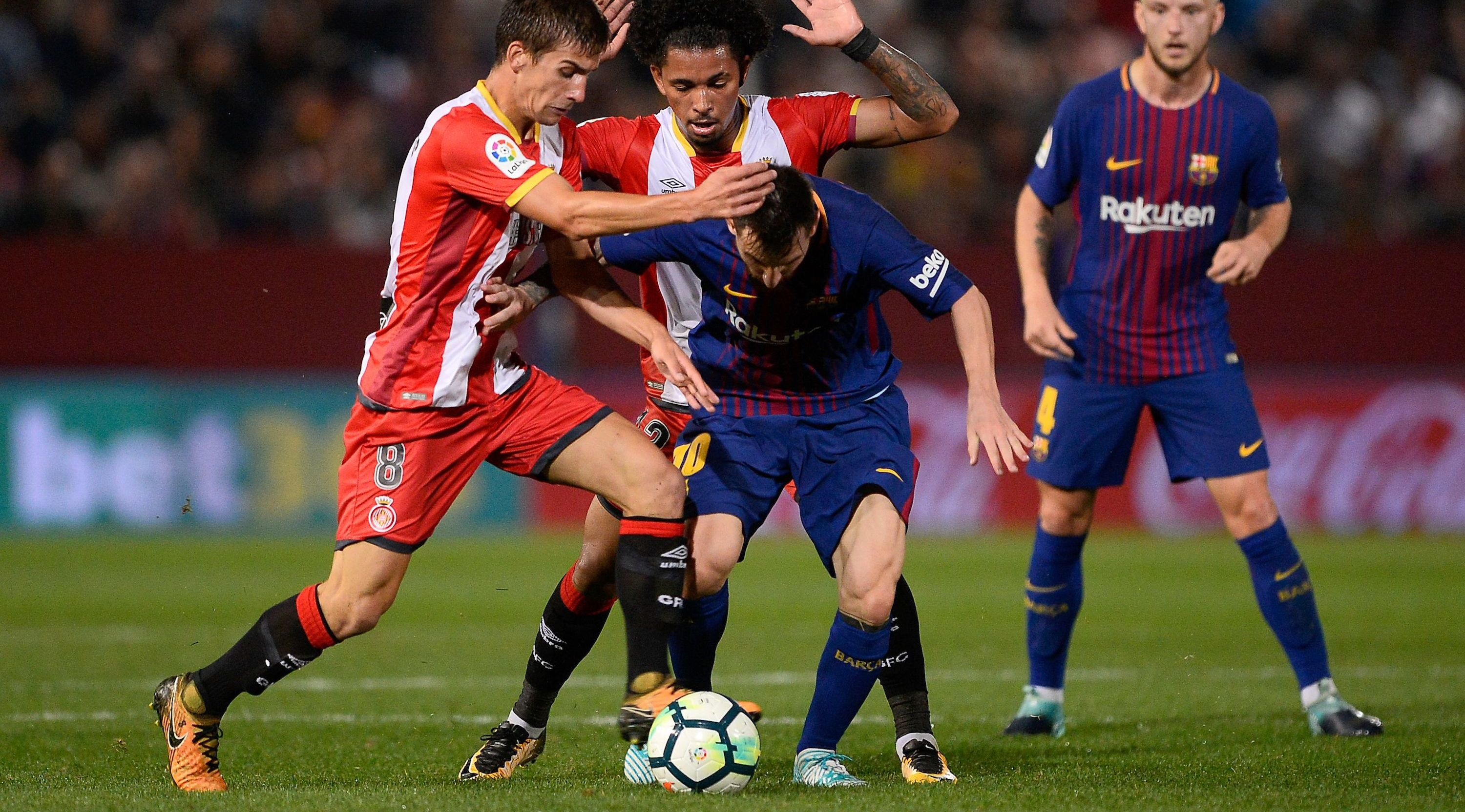 Barcelona's forward from Argentina Lionel Messi (C) vies with Girona's midfielder Pere Pons (L) and Girona's midfielder Alex Granell during the Spanish league football match Girona FC vs FC Barcelona at the Montilivi stadium in Girona on September 23, 2017. / AFP PHOTO / Josep LAGO (Photo credit should read JOSEP LAGO/AFP/Getty Images)