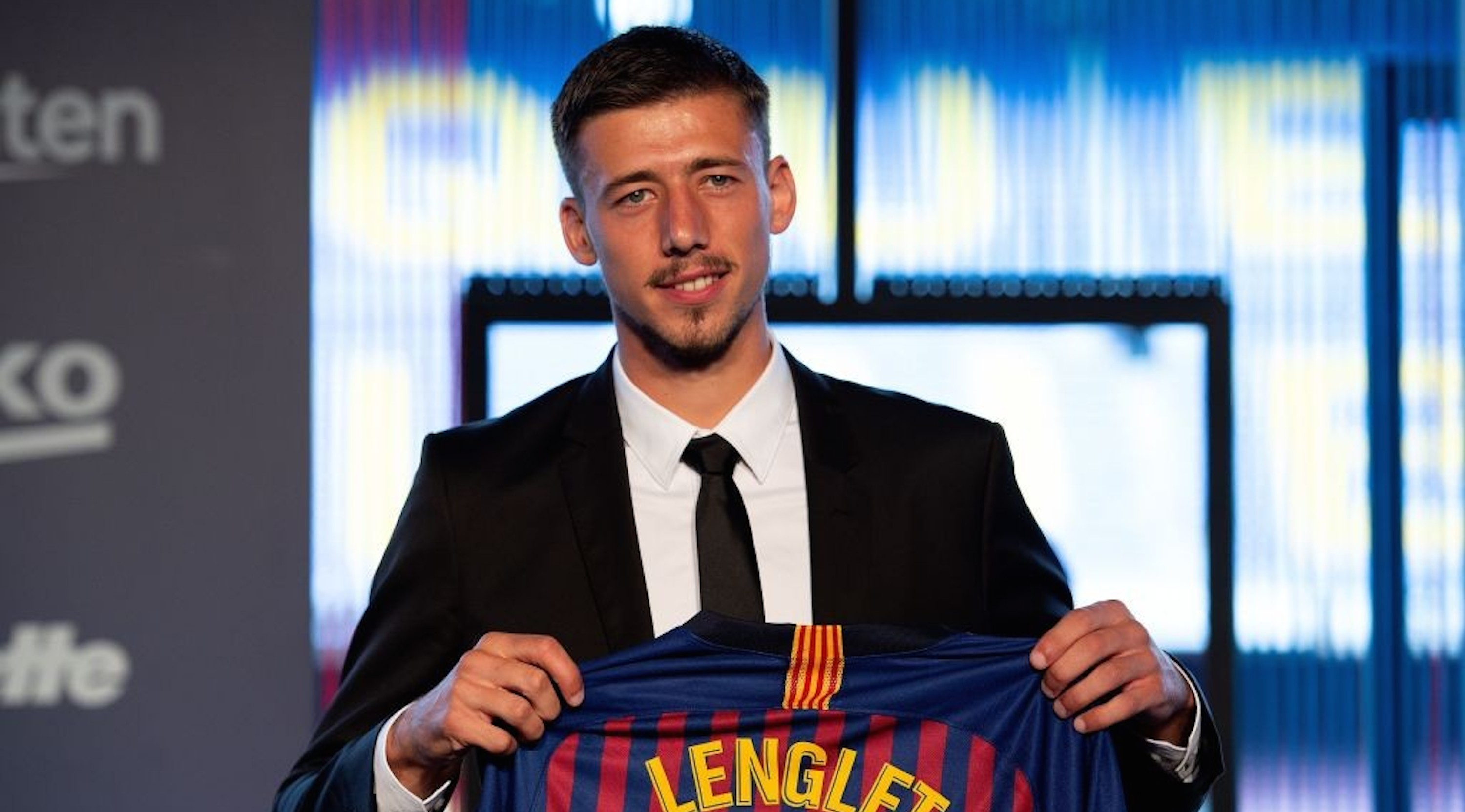 Barcelona«'s new player French defender Clement Lenglet poses with his new jersey during his official presentation at the Camp Nou stadium in Barcelona on July 13, 2018. - Clement Lenglet will join up with compatriots Samuel Umtiti and Ousmane Dembele at Barcelona in a transfer from La Liga rivals Sevilla worth 35.9 million euros ($42 million), the club said. The 23-year-old has signed a five-year contract with a buyout clause valued at 300 million euros, it added. (Photo by Josep LAGO / AFP) (Photo credit should read JOSEP LAGO/AFP/Getty Images)