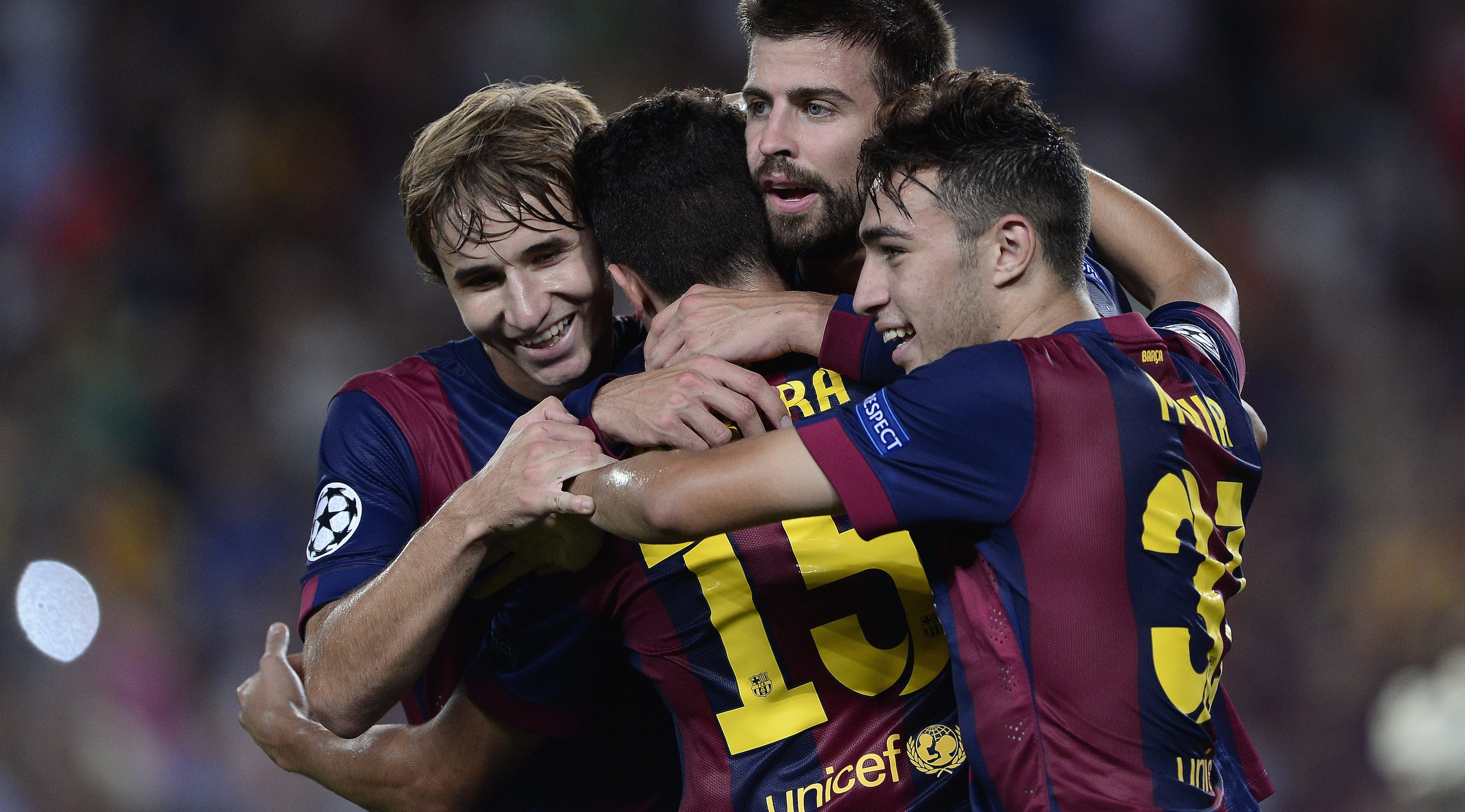 Barcelona's defender Gerard Pique (C) celebrates with Barcelona's midfielder Sergi Samper (L) and Barcelona's forward Munir (R) after scoring during the UEFA Champions League football match FC Barcelona vs APOEL FC at the Camp Nou stadium in Barcelona on September 17, 2014. AFP PHOTO / JOSEP LAGO (Photo credit should read JOSEP LAGO/AFP/Getty Images)