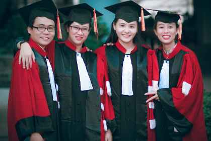 man and women wearing red and black academic gowns and black mortar boards