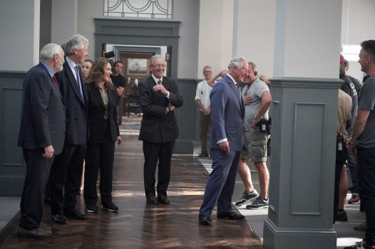 UNIVERSAL SELECT Prince Charles visits B25 at Pinewood Studios 20/6/2019 accompanied by The Lord Lieutenant of Buckinghamshire, Sir Henry Aubrey-Fletcher and Producers, Michael G. Wilson and Barbara Broccoli takes time to meet with crew members on the MI6 set
