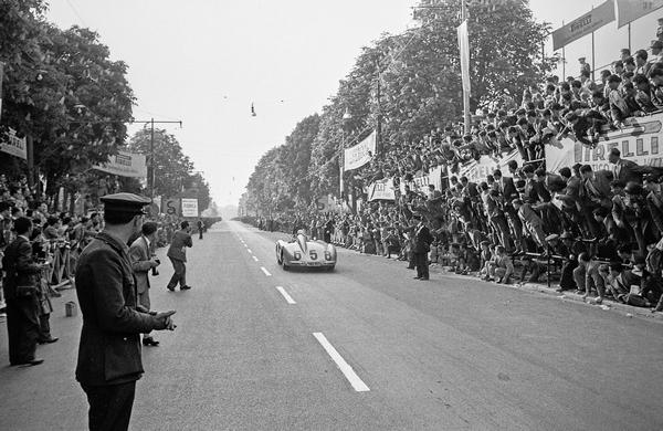 Juan Manuel Fangio (Startnummer 658) kurz nach dem Start zur Mille Miglia 1955 in Brescia im Mercedes-Benz Typ 300 SLR Rennsportwagen (W 196 S). Er beendet das Rennen als Zweiter, hinter Stirling Moss und Denis Jenkinson ebenfalls auf 300 SLR Rennsportwagen. Juan Manuel Fangio (start number 658) just after the start of the 1955 Mille Miglia in Brescia in a Mercedes-Benz 300 SLR racing sports car (W 196 S). He finished the race in second place, behind Stirling Moss and Denis Jenkinson, also in a 300 SLR racing sports car.