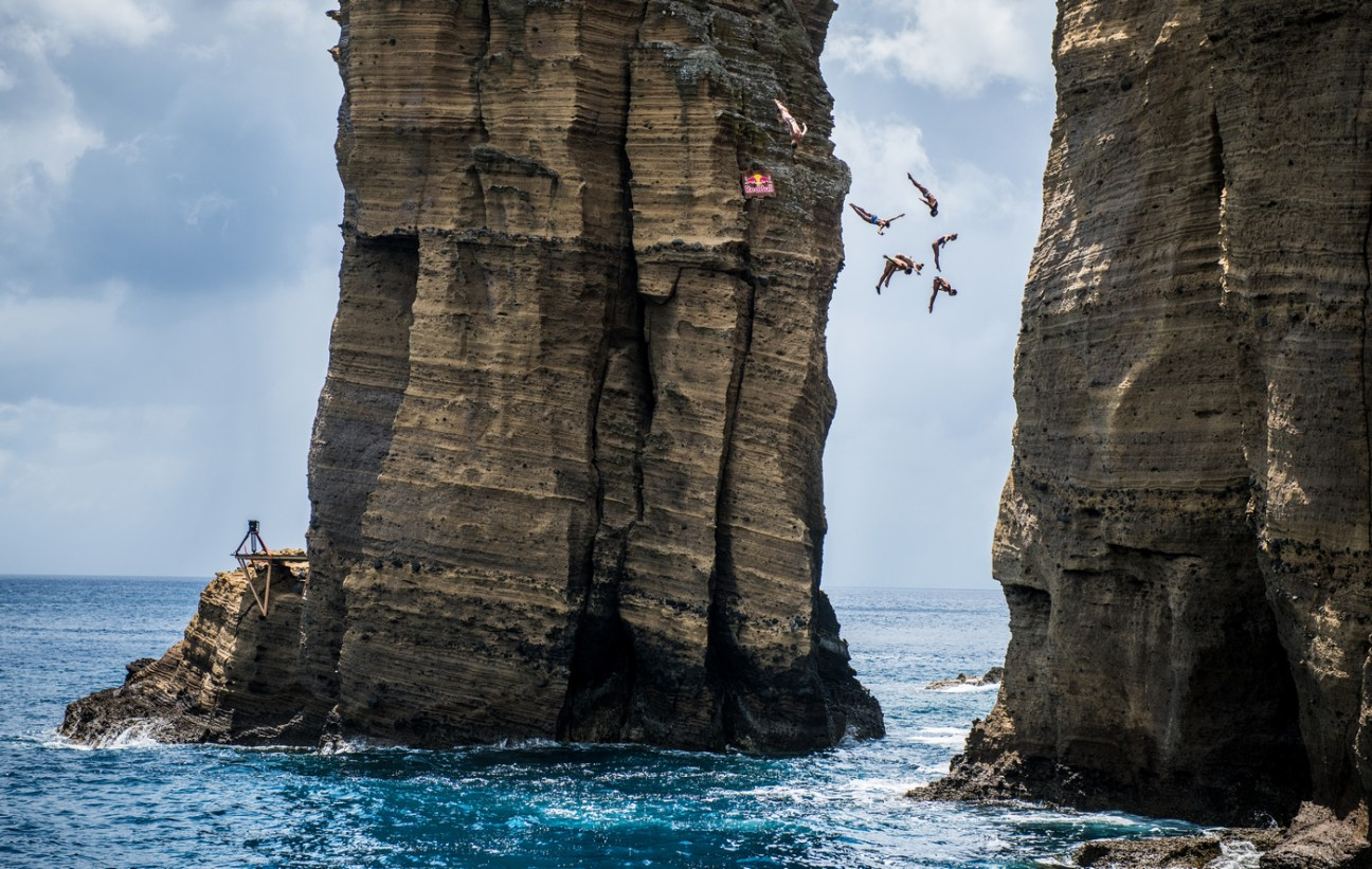 Nikita Fedotov of Russia, Lysanne Richard of Canada, Slavik Kolesnikov of the Ukraine, Jessica Macaulay of the UK, Todor Spasov of Bulgaria, Robin Georges of France and Ellie Townsend Smart of the USA dive from the rock monolith at Islet Vila Franca do Campo after the first training session of the third stop at the Red Bull Cliff Diving World Series in Sao Miguel, Azores, Portugal on July 12, 2018. // Romina Amato/Red Bull Content Pool // AP-1W8R9RG6D2111 // Usage for editorial use only //