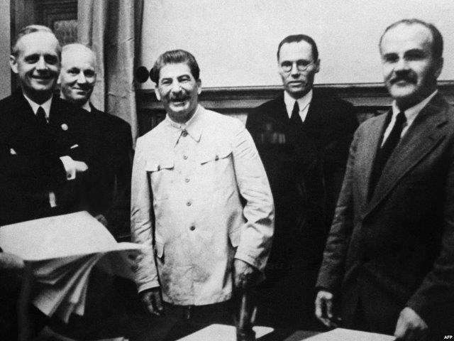 German Foreign Minister Joachim Von Ribbentrop (left), Soviet leader Joseph Stalin, and his Foreign Minister Vyacheslav Molotov (right) in the Kremlin signing the pact dividing Europe between Hitler's and Stalin's regimes on August 23, 1939.
