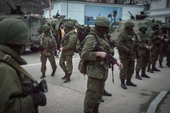 Armed Russian soldiers block the entrance to a Ukrainian naval border guard base in Sevastopol during the annexation of the Crimea region of Ukraine. March 2014. (Image: New York Times)