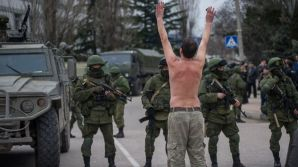 An unarmed Ukrainian man stands in protest in front of spetsnaz soldiers of Putin's occupation force capturing Crimea, February 2014.