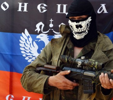 "A member of the ""DNR"" unit of Russia's hybrid army in Ukraine in front of the unit's flag"