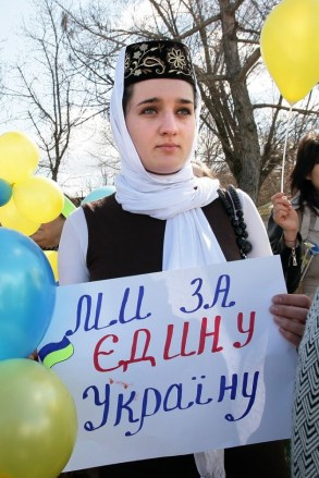 A girl in a national Crimean Tatar dress holds a placard during a protest against the presence of Russian troops in Crimea, Bakhchysaray, Crimea, March 5, 2014 (Image: mfa.gov.ua)