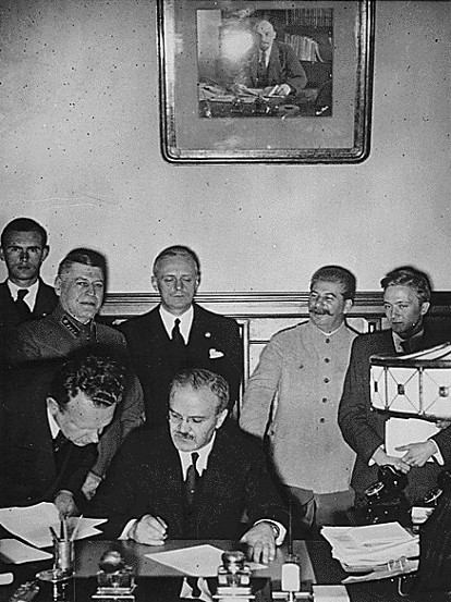 The German foreign minister, Joachim von Ribbentrop (third from right), watches his Soviet counterpart Vyacheslav Molotov (seated) sign the Molotov-Ribbentrop Pact of non-aggression on Aug. 23, 1939. AP Photo