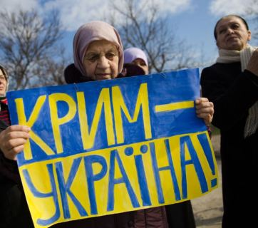 "A Crimean Tatar woman holds a sign ""Crimea Is Ukraine"" in protest to the fake ""referendum"" imposed by force by Moscow in March 2014."
