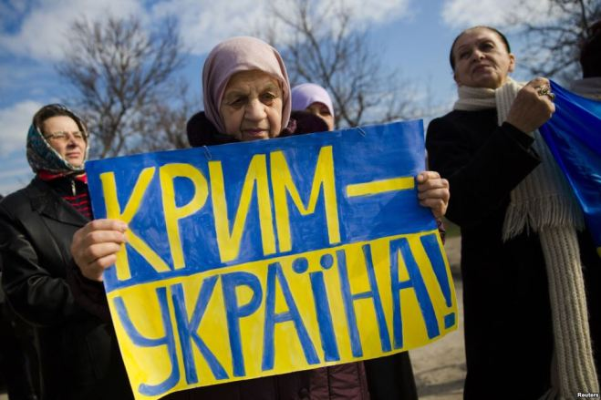 """A Crimean Tatar woman holds a sign """"Crimea Is Ukraine"""" in protest to the fake """"referendum"""" imposed by force by Moscow in March 2014."""