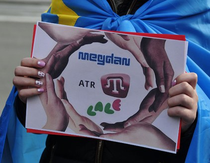 A protester in Europe wearing a Crimean Tatar flag with a sign protesting the shuttering of Crimean Tatar media outlets by Russian occupiers in April 2015 (Photo: Olexei Ivanov, day.kiev.ua)
