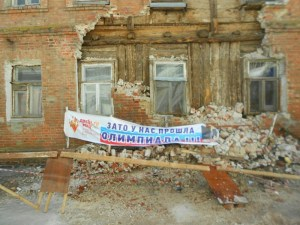 """Residents of an apartment building collapsing due to the lack of government maintenance in the city of Saratov, Russia put up the sign that says: """"But We Hosted The Olympics!"""" (Image: om-saratov.ru, April 2015)"""