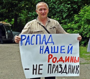 "A protestor against the Day of Russia celebration in the city of Penza, Russia on June 12, 2015. The sign says ""Our Motherland falling apart is not a holiday!"" (Image: social media)"
