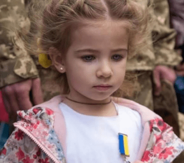 "The photo of a little girl receiving the metal of her father, Andriy Matviyenko, killed in the Donbas, that was massively blocked by Facebook ""for nakedness."""