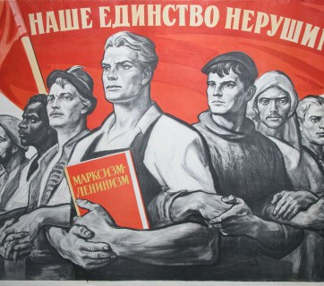 "The old Soviet propaganda poster says: ""Our union is indestructible!"" The central figure in the poster depicts a Russian worker holding a book named ""Marxism Leninism."""