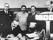 Stalin supervising the signing of the so-called Molotov-Ribbentrop Pact dividing Poland between Hitler's regime and his own, Aug 23, 1939. From left to right: Joachim von Ribbentrop, German Minister of Foreign Affairs; Vyacheslav Molotov, Soviet Minister of Foreign Affairs (sitting); Joseph Stalin, Soviet dictator; Vladimir Pavlov, First Secretary of the Soviet embassy in Germany (Image: TASS)