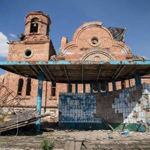 Devastation in the Donbas brought by the Russian military aggression in Ukraine. This picture taken on April 23, 2015 shows a bus stop and a church damaged by artillery shelling, in the village of Peski near Donetsk. (Image: Oleksandr Ratushniak / AFP)