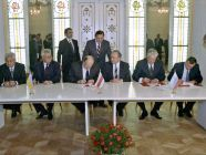 """Signing the Agreement to eliminate the USSR and establish the Commonwealth of Independent States. Ukrainian President Leonid Kravchuk (second from left seated), Chairman of the Supreme Council of the Republic of Belarus Stanislav Shushkevich (third from left seated) and Russian President Boris Yeltsin (second from right seated) during the signing ceremony to eliminate the USSR and establish the Commonwealth of Independent States. Viskuly Government Retreat in the Belarusian National Park """"Belovezhskaya Pushcha"""" on on December 8, 1991. (Image: U. Ivanov, RIAN archives via Wikipedia)"""