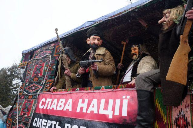 Masks of UPA partisans inhabit a float bearing the UPA flag