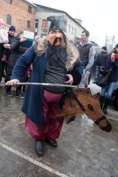 A mask playing a kozak jumps around on his wooden horse