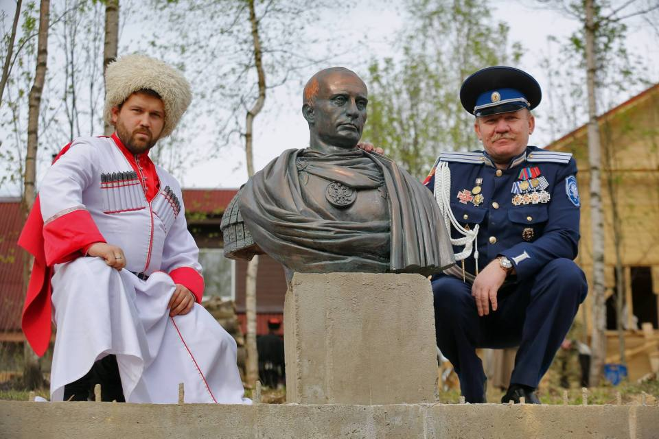 Russian neo-Cossack paramilitaries pose by a Putin monument in St. Petersburg, Russia