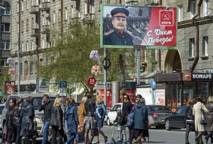 People walk past the poster with WWII Soviet dictator Josef Stalin which was sponsored by local branch of the Communist Party celebrating Victory Day in Novosibirsk, Russia, Thursday, May 5, 2016, about 2800 kms (1,750 miles) east of Moscow. Russia celebrates victory in WWII on May 9. (AP Photo/Ilnar Salakhiev)