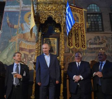 Vladimir Putin visiting Karyes, the Orthodox enclave of Mount Athos. The above photo, of Putin standing at an ancient throne alongside Greek officials and Orthodox dignitaries, was described by various Russian news outlets, both within the country and abroad, as Putin standing at a place which had until now been reserved only for Byzantine emperors. (Image: life.ru)