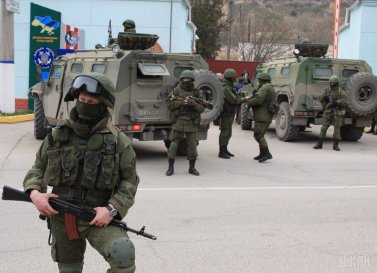 "At first, Putin claimed there were the ""little green men"" in Crimea, not the Russian military, as he admitted a year later. Russian special services troops besieging a Ukrainian military base in Crimea, February 2014. (Image: UNIAN)"