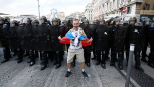 A Russian football/soccer fan posing with a national flag in front of French police protecting the order at the 2016 UEFA European Cup in France, June 2016 (Image: social media)