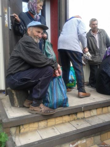 Elderly locals queuing at a soup kitchen