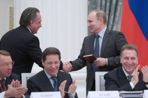 Vladimir Putin congratulating Russia's sports minister Vitaly Mutko (believed to be the top administrator of the state-organized doping system) with his birthday at a joint meeting of the Council for Physical Education and Sports under the President of Russia and the Organizing Committee for the 2018 FIFA World Cup. The book Putin holds in his hand is an English language self-study textbook being presented to Mutko as a prank gift. December 2015, Moscow, Russia (Image: Mikhail Metzel/TASS)