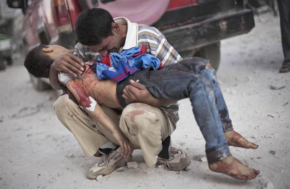 A Syrian man cries while holding the body of his son near Dar El Shifa hospital in Aleppo, Oct. 3, 2016. (Image: Manu Brabo / AP)
