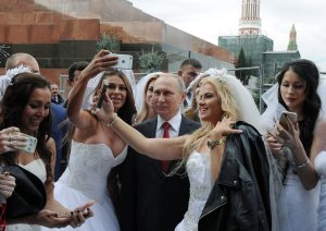 "Vladimir Putin at a staged photo shoot with Russian models posing as brides, which was later presented to Russian and foreign media as Putin's random encounter with a group of real brides who charmed him to take some ""selfies"" while encircled by bodyguards. Red Square in Moscow, September 2016 (Image: TASS)"