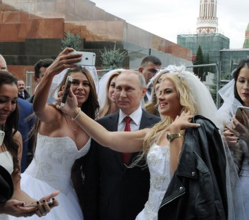 "Vladimir Putin at a staged photo shoot with models posing as brides, which was later presented to Russian and foreign media as Putin's random encounter with a group of real brides who charmed him to take some ""selfies"" while encircled by bodyguards. Red Square in Moscow, September 2016 (Image: TASS)"