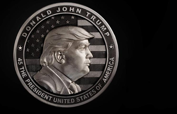 """A two-pound coin dedicated to Donald Trump created in Russia for his inauguration. The back of the coins shows the Statue of Liberty against a background of the American flag with inscription reading, """"In Trump We trust."""" (Image: Art Grani)"""
