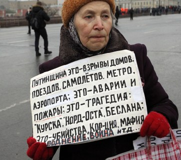 """A woman at the 2015 Boris Nemtsov Memory March on 1 March 2015 in Moscow, Russia. Her sign says: """"Putinism it is explosions of apartment buildings, airplanes, metro stations, airports; it is incidents and fires; it is tragedies of 'Kursk,' 'Nord-Ost,' Beslan; it is murders, corruption, mafia, war..."""" (Image: kykyryzo.ru)"""
