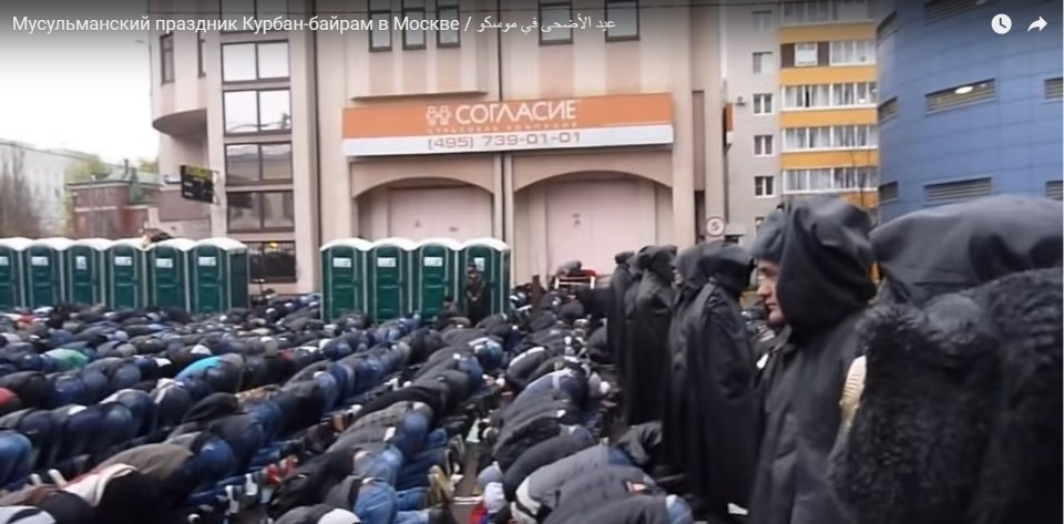 A collective prayer during the Kurban Bayram Muslim festival in Moscow. Due to the dire shortage of mosques in the city, the faithful pray under the rain in the street while Russian policemen in black rain coats watch over them. (Image: video capture)