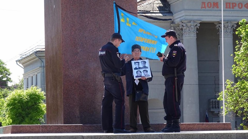 Russian policemen detain Crimean Tatar activist Server Karametov, who stood with the national flag and the photos of his deported parents at the central square of occupied Simferopol. He was not even allowed to lay flowers on the monument to the 1944 victims. Photo: Anton Naumlyuk