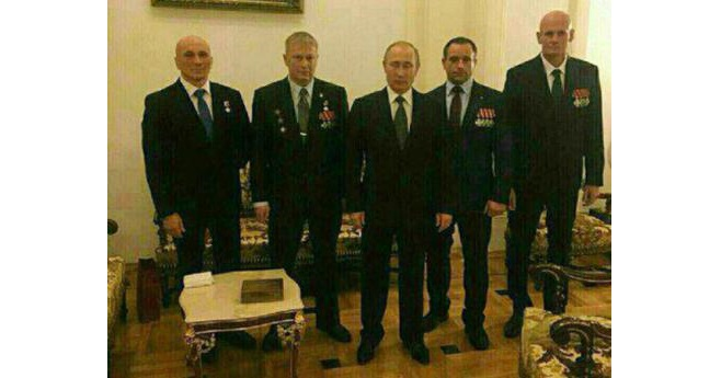 """Russian president Vladimir Putin pictured with Dmitry Utkin (""""Wagner"""") on the far right and other commanders of the Wagner private military company that fights on orders of the Russian military in Ukraine and Syria, but is not a part of it formally. This image is believed to date from December 2016."""