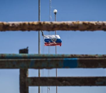 A Russian state flag flying in Moscow-annexed Crimea next to its neglected and rusting infrastructure (Image: Alina Smutko, krymr.org/RFE/RL)