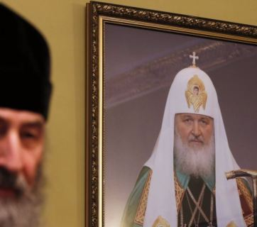 Metropolitan Onufriy of the Ukrainian Orthodox Church of the Moscow Patriarchate in his office standing next to the photograph of Patriarch Kirill, the head of the Moscow Patriarchate. (Image: UNIAN)