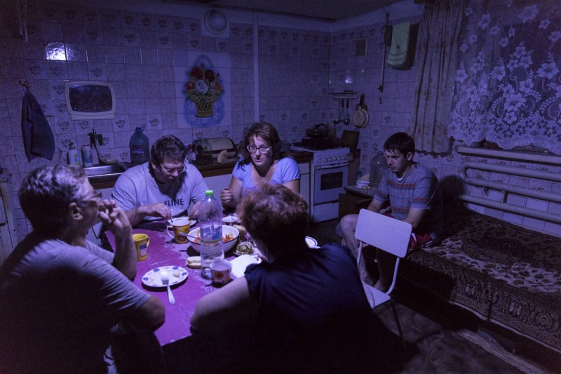 Lebedev and family have dinner under a solar powered light as the fighting begins nearby.