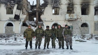 Donetsk resident Oleksiy Bogdanov (in the middle, in black hat) in the foreground of a residential house in Vuhlehirsk, which was destroyed by the Russian artillery amid the Battle for Debaltseve.