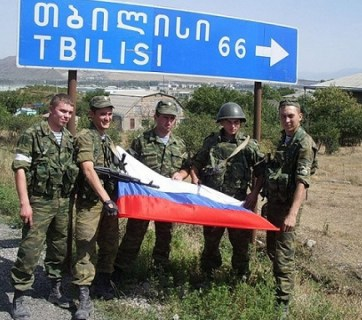 Russian soldiers invading Georgia taking photographs by the road sign showing 66 kilometers to the country's capital Tbilisi. August 2008. Photo: Social media